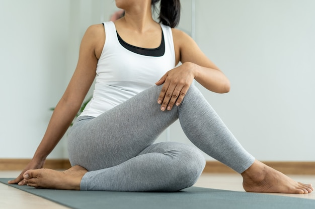 Young woman doing stretching exercises at home in relaxation.