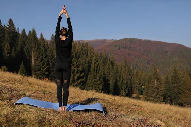 Молодая женщина делает упражнения на растяжку на природе в горах. спортивная девушка практикующих йогу ставят в леггинсы. красивый лесной пейзаж