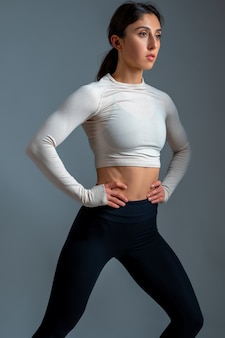 Young woman doing stretching lunge on grey wall