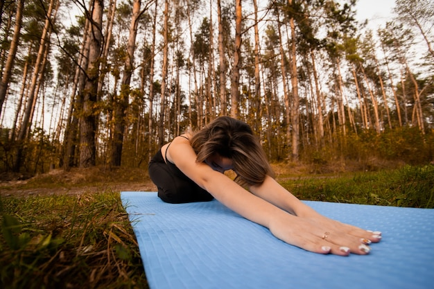 Young woman doing stretching workout on fitness mat. relax time. workout between pine trees. forest of park on background. healthy lifestyle concept. athletic woman meditating in child yoga pose.