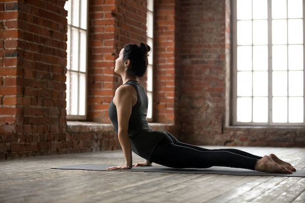 Young woman doing upward facing dog exercise