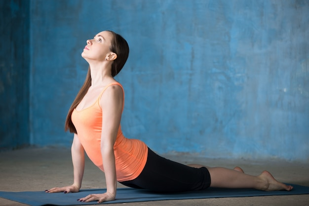 Young woman doing upward-facing dog pose
