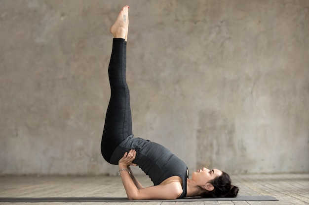 Young woman doing viparita karani exercise