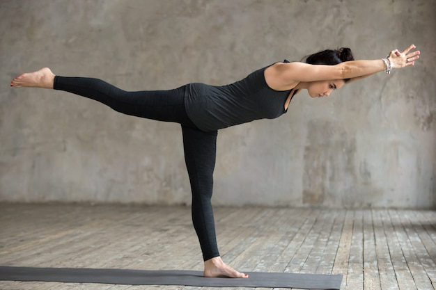 Young woman doing virabhadrasana 3 exercise
