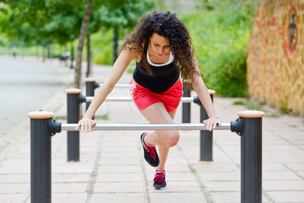 Young woman doing warm up exercises outdoors