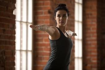Молодая женщина делает упражнение Воин II, крупный план