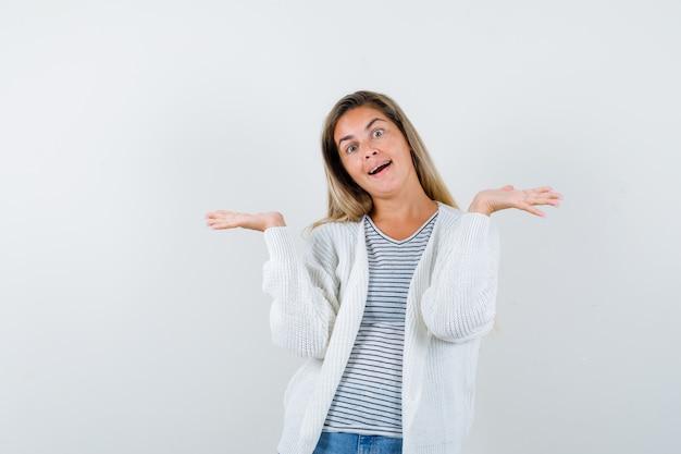 Tシャツ、ジャケット、陽気に見える、正面図でウェルカムジェスチャーをしている若い女性。