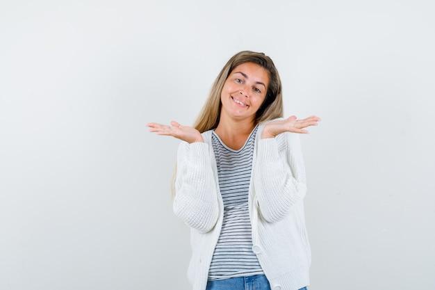 Giovane donna che fa gesto di benvenuto in maglietta, giacca e sembra allegra. vista frontale.