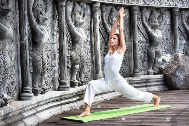 Young woman doing yoga in abandoned temple on wooden platform. practicing in thailand