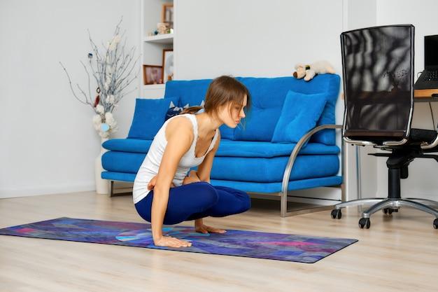교차 다리와 요가 팔 균형 운동을 하 고 젊은 여자