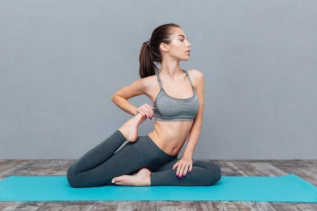 Young woman doing yoga asana eka pada rajakapotasana (one legged king pigeon) isolated on grey background