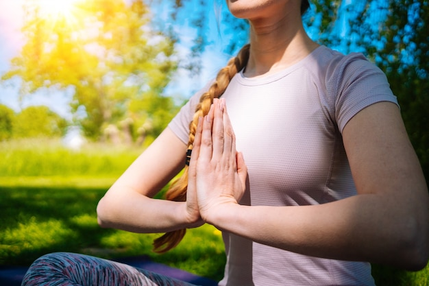 Молодая женщина делает асаны йоги в парке девушка растягивает упражнения в позе йоги счастливая и здоровая женщина, сидящая в позе лотоса и практикующая йогу, медитацию и спорт на закате на открытом воздухе