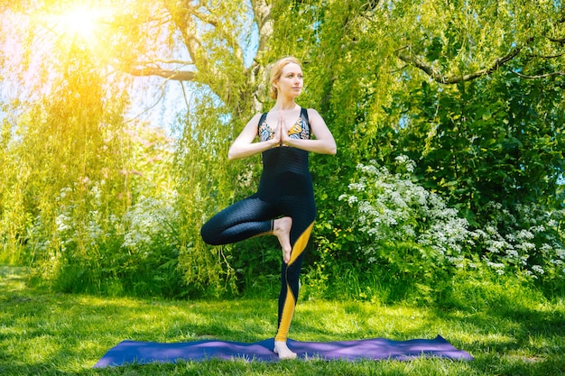 Young woman doing yoga asana in park girl stretching exercise in yoga position happy and healthy wom...