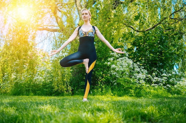 Young woman doing yoga asana in park girl stretching exercise in yoga position happy and healthy woman sitting in lotus position and practicing yoga meditation and sport on sunset outdoors