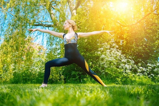 Young woman doing yoga asana in park girl stretching exercise in yoga position happy healthy woman
