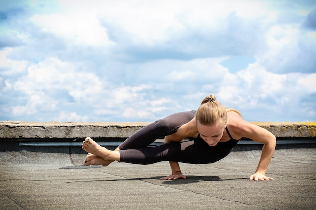 Young woman doing yoga, ashtavakrasana