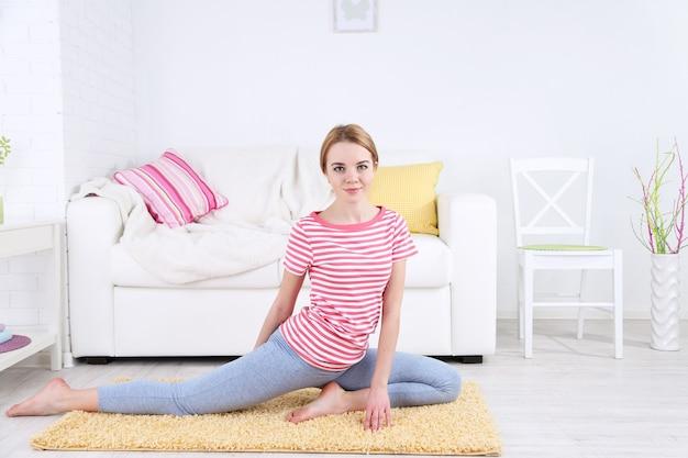 Молодая женщина занимается йогой дома