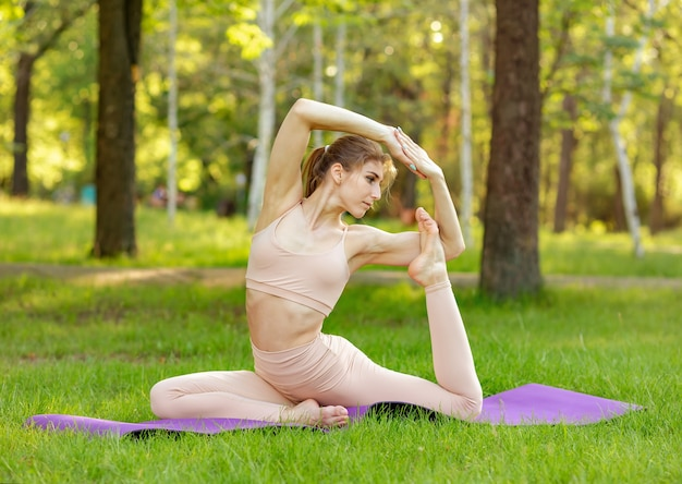 Молодая женщина делает упражнения йоги и расслабляется в утреннем зеленом парке