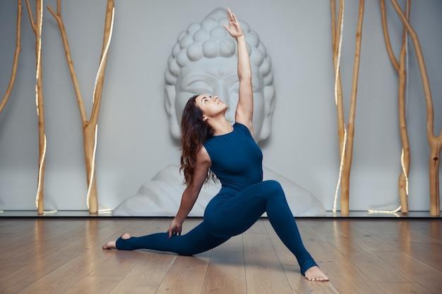 Молодая женщина делает упражнения йоги в студии