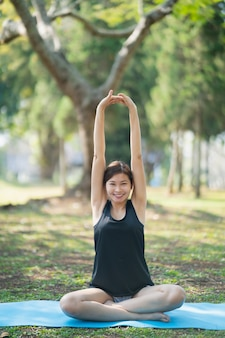公園で屋外でヨガの練習をしている若い女性、スポーツヨガの概念
