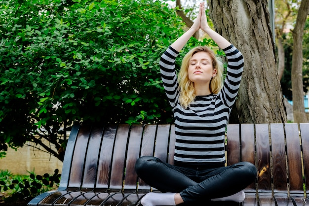 Young woman doing yoga exercise sitting on a bench in a park in striped top and black jeans