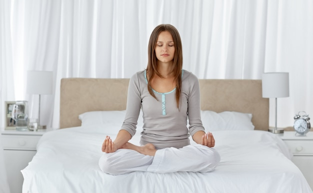 Young woman doing yoga exercises on the bed