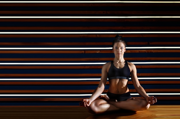 Young woman doing yoga exercises in dark studio. health lifestyle concept.