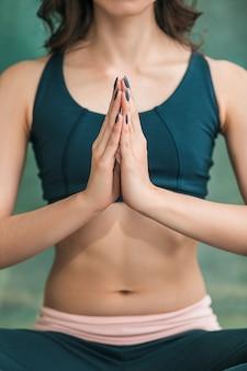 Young woman doing yoga exercises on green wall