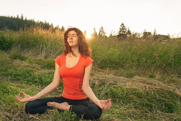 Young woman doing yoga exercises in the nature