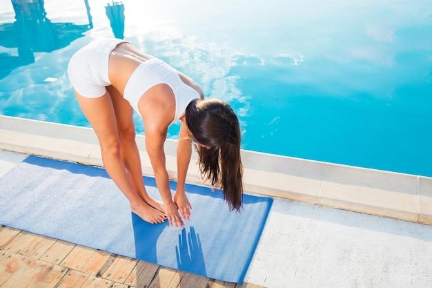 屋外でマットの上でヨガの練習をしている若い女性