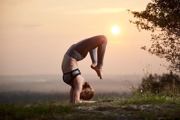일몰에 야외에서 요가 연습을 하 고 젊은 여자