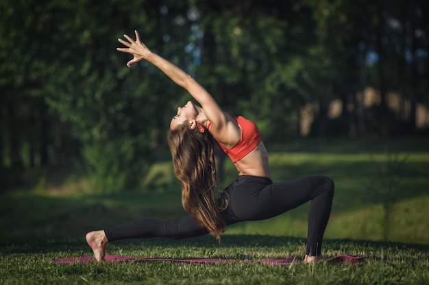 Young woman doing yoga exercises in the summer city park