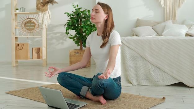 Молодая женщина делает упражнения йоги с помощью ноутбука, сидя на полу дома