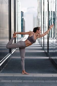 Young woman doing yoga exercises with city on background.