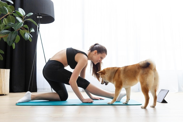 Young woman doing yoga next to her dog