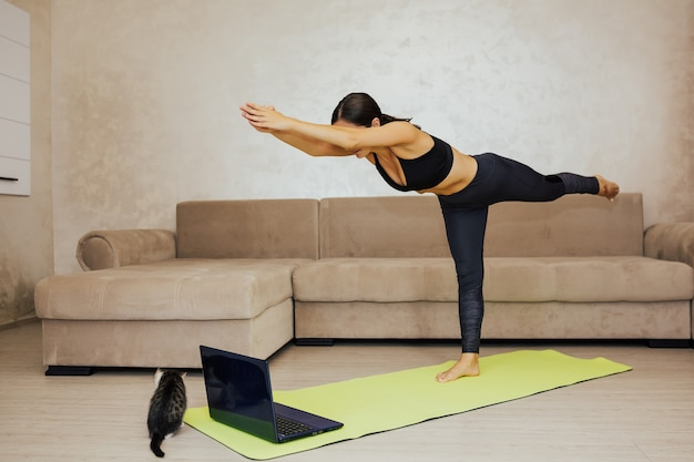 Young woman doing yoga at home. she practicing yoga, doing warrior iii exercise, virabhadrasana 3 pose