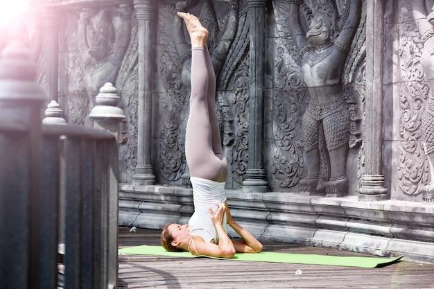 木製のプラットフォーム上の放棄された寺院でヨガをしている若い女性。タイでの練習