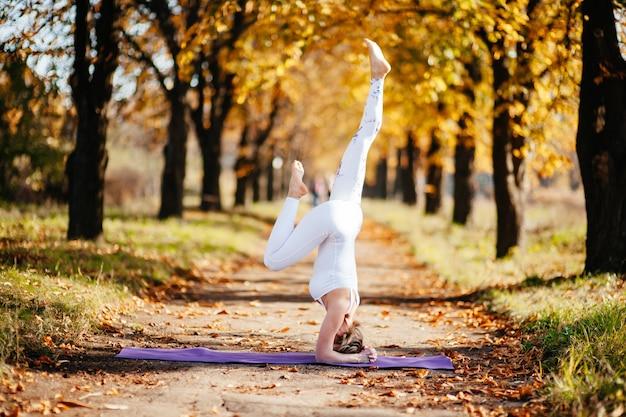 Молодая женщина занимается йогой в осеннем городском парке возле желтых березов