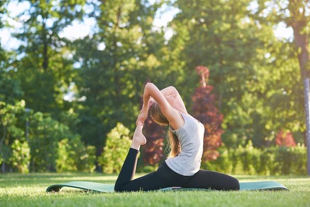 지역 공원 생활 건강한 활동적인 스포츠맨 조화 개념에서 아침에 요가 하 고 젊은 여자.