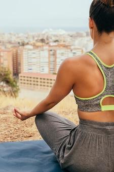 Giovane donna facendo yoga e meditare
