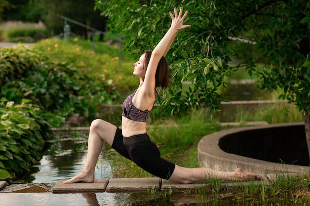 Young woman doing yoga in the morning park, near a small decorative lake.