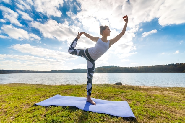 瞑想、屋外の湖の近くでヨガを行う若い女性。スポーツフィットネスと自然の中での運動。秋の夕日。