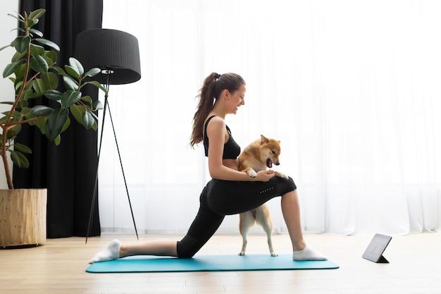 Молодая женщина занимается йогой рядом со своей собакой