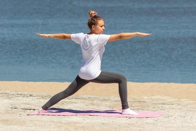 Молодая женщина занимается йогой на розовом коврике у моря
