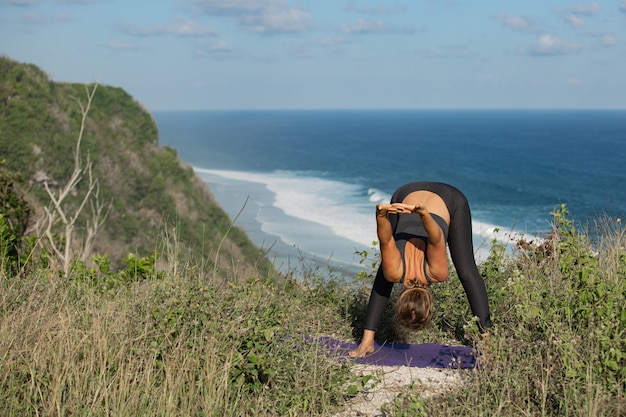 Young woman doing yoga outdoors with amazing back view. bali. indonesia.