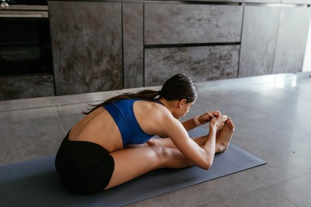 Giovane donna che fa esercizio di posa di yoga a casa, stile di vita sano