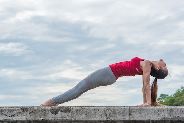 Young woman doing yoga pose in natural park.