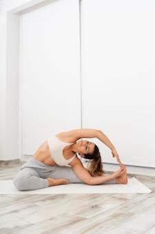 Giovane donna che fa una posa di yoga su una stuoia bianca