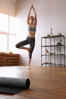Молодая женщина делает позу дерева йоги, врикшасана