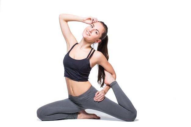 Giovane donna che fa yoga su priorità bassa bianca